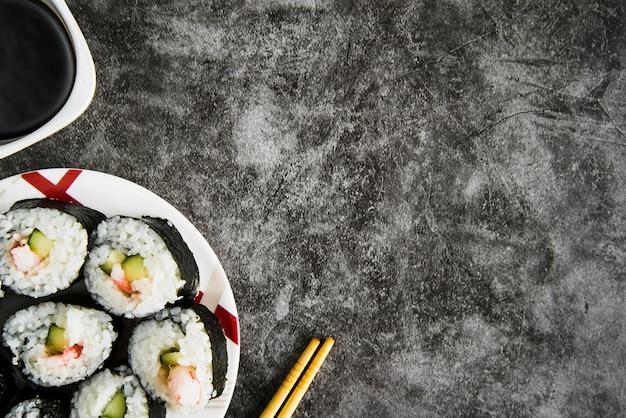Mesa con rollos de sushi, salsa de soja y palillos de madera.