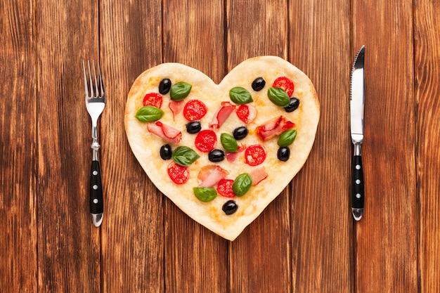 Mesa romántica con pizza y vajilla.