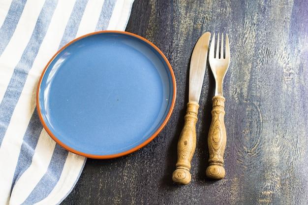 Mesa rústica con plato y cubiertos.