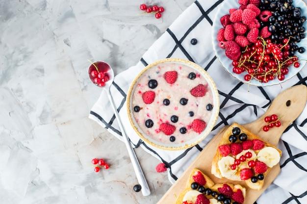 Una mesa con un saludable desayuno de verano: avena con moras, grosellas y frambuesas.