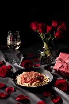 Mesa de san valentín con pasta y ramo de rosas.