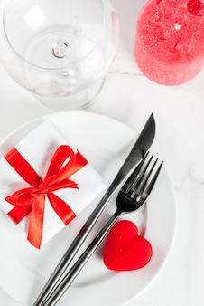 Mesa de san valentín con plato, tenedor, cuchillo, caja de regalo y corazón rojo, sobre mármol blanco copyspace