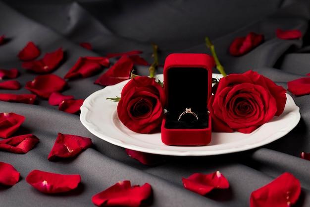 Mesa de san valentín con rosas y anillo de compromiso en placa