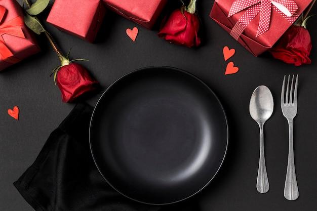 Mesa de san valentín con rosas y plato.