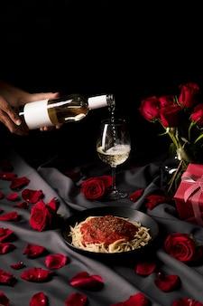 Mesa de san valentín con vino y pasta.