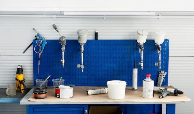 Mesa en servicio de automóviles con aerógrafos para pintar automóviles, pistola en taller de reparación de automóviles