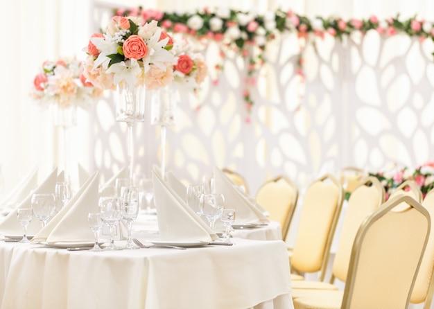 Mesa servida para la cena del evento con cubiertos y vasos, decorada con composiciones florales en jarrones.