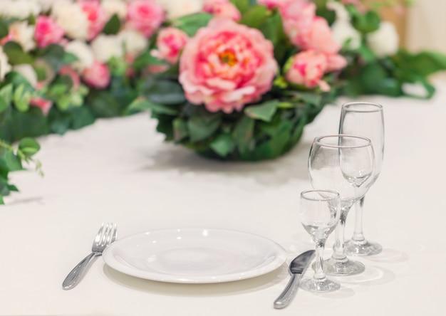 Mesa servida para una persona con un juego de vasos, decorada con flores naturales. cena de evento