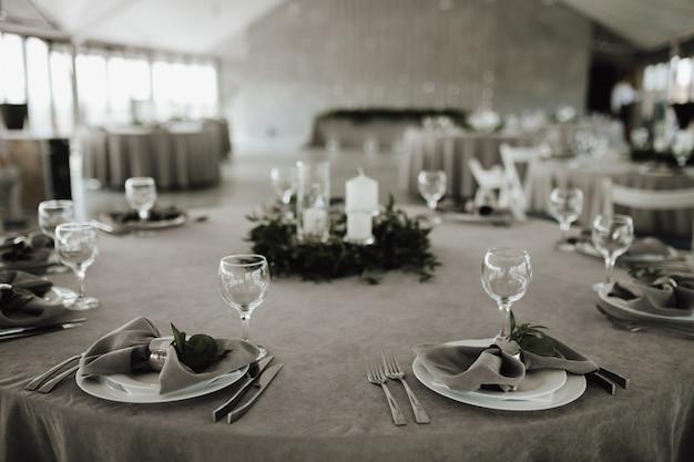 Mesa con servilletas grises, cubiertos, tenedores y vasos, decorada con vegetación y velas.