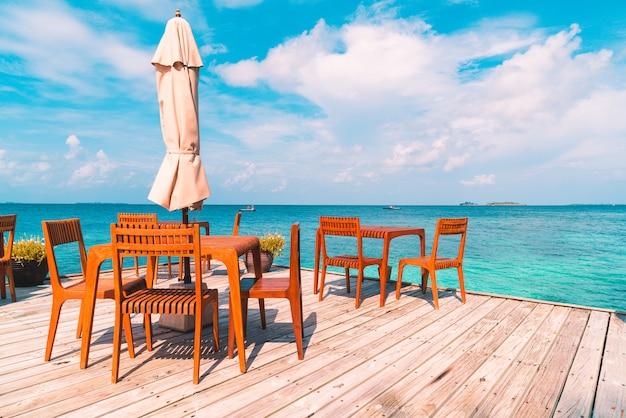 Mesa y silla de madera con fondo de vista al mar en maldivas
