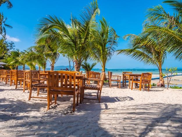 Mesa y silla de madera en la playa.