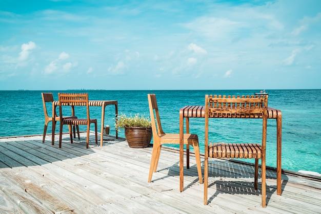 Mesa y silla de madera con vistas al mar en maldivas