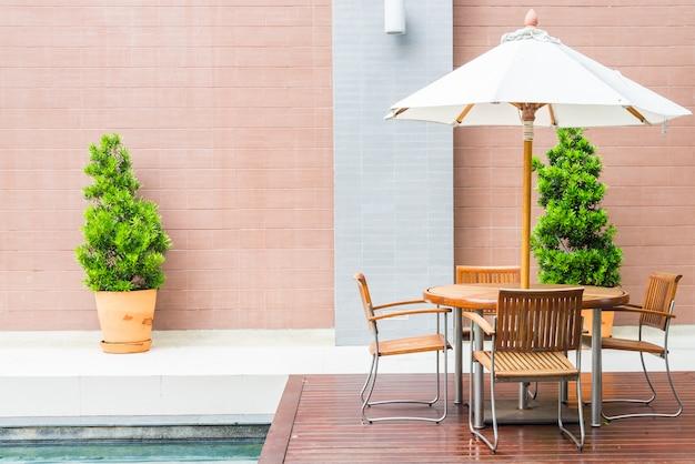 Mesa y silla con sombrilla blanca, patio exterior.