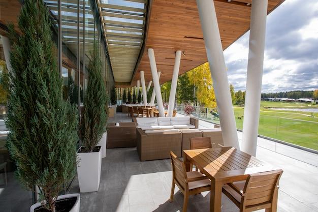 Mesa y sillas de madera, sofás y árboles decorativos verdes que crecen en macetas de pie al aire libre a lo largo de grandes ventanales del moderno centro de negocios