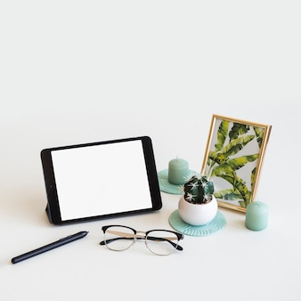Mesa con tableta cerca de marco de fotos, bolígrafo y gafas.