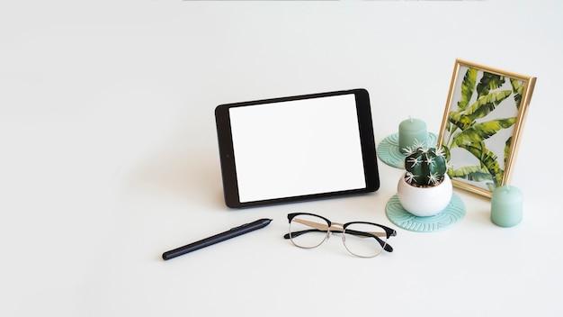 Mesa con tableta cerca de marco de fotos, cactus, pluma y lentes.