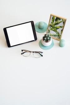 Mesa con tableta cerca de marco de fotos, planta de interior y gafas.