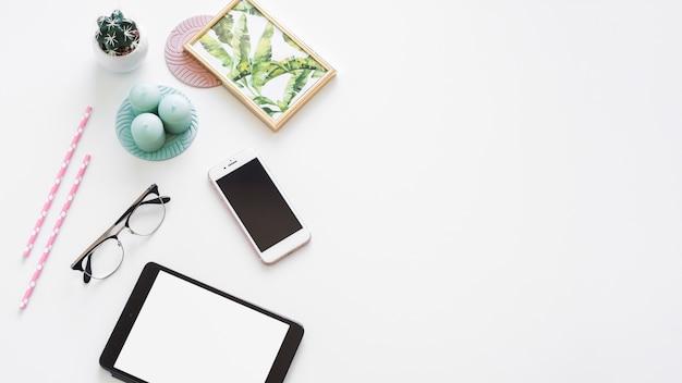 Mesa con tableta cerca de marco de fotos, planta de interior, velas y anteojos