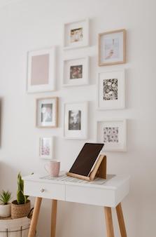 Mesa con una tableta sobre ella y con el fondo de pared decorada