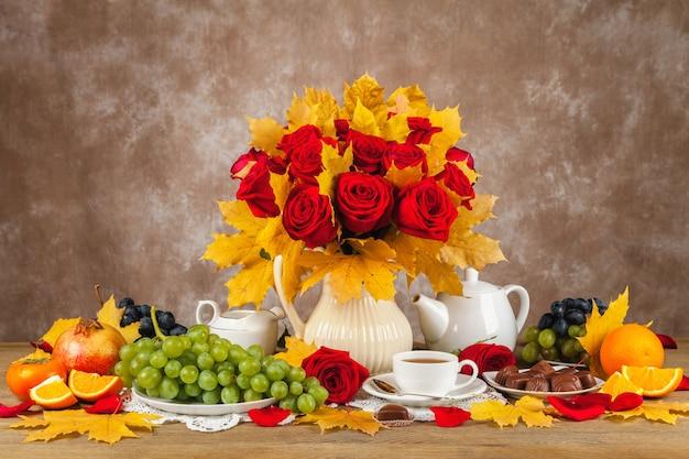 Mesa con tazas de té, bombones y un ramo.