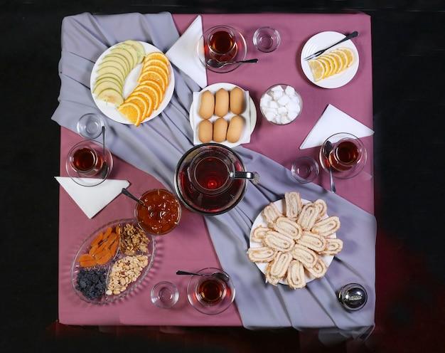 Mesa de té con té y una variedad de dulces y aperitivos sobre el mantel violeta.