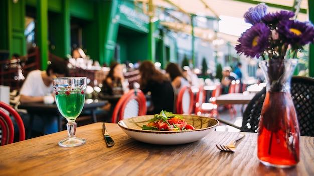 Mesa de terraza de verano con platos y invitados de cristal.