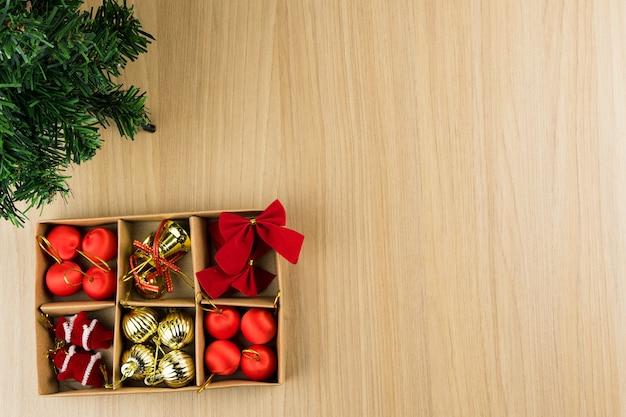 Mesa con textura de madera clara con pequeño árbol de navidad y caja con los adornos colgantes.
