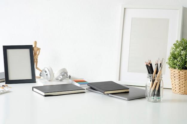 Mesa de trabajo de artista con lápiz, libro de dibujo, marco de foto y decoración de la planta.