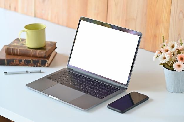 Mesa de trabajo blanca con computadora portátil con pantalla en blanco, flor, libros y taza de café