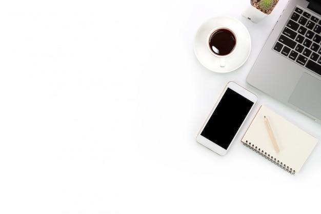 Mesa de trabajo blanca con computadora portátil y teléfono celular