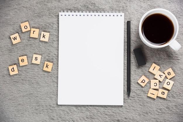 Mesa de trabajo de bloques de madera con libreta espiral en blanco; lápiz; taza de goma y café sobre fondo gris