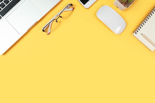 Mesa de trabajo con computadora y útiles de oficina en amarillo