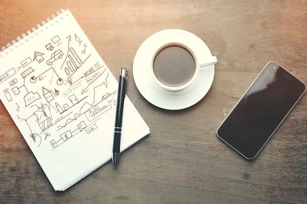 Mesa de trabajo: cuaderno, bolígrafo, teléfono y taza de café en la mesa de madera