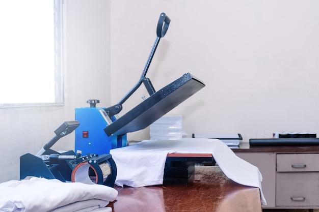 Mesa de trabajo de estampación de camisetas y planchado o sublimación. concepto de diseño gráfico y publicidad.