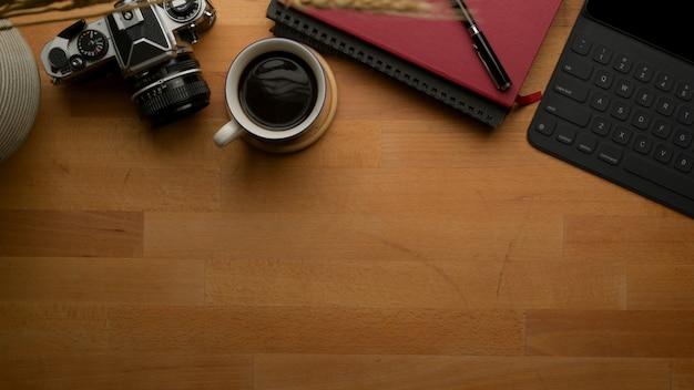 Mesa de trabajo de fotógrafo con espacio de copia con cámara, tableta, libros de horarios, taza de café y decoración