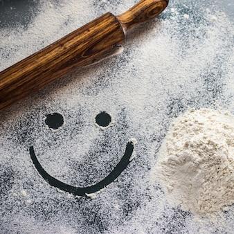Mesa de trabajo con harina, rodillo y cara sonriente.