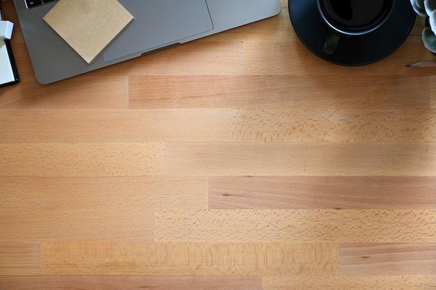 Mesa de trabajo de madera con laptop, café y espacio de copia.