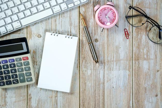 Mesa de trabajo de madera con teclado portátil, calculadora, reloj, cuaderno y suministros