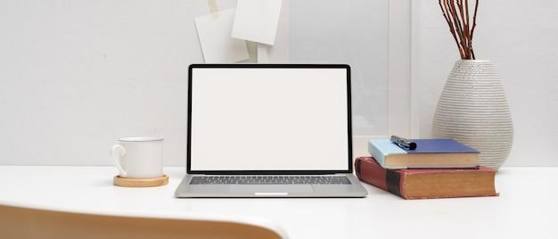 Mesa de trabajo mínima con maqueta portátil, libros, taza de café y decoraciones.