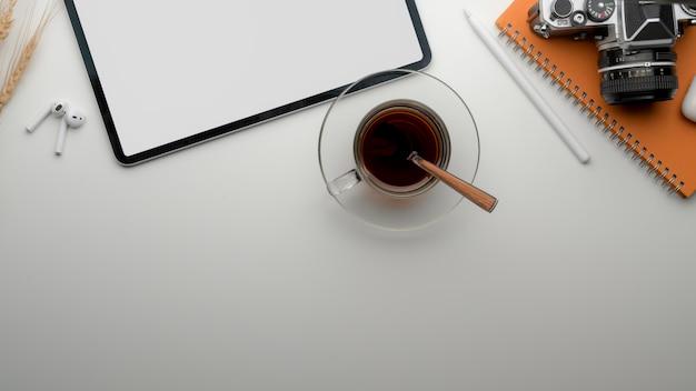 Mesa de trabajo moderna con tableta de pantalla en blanco, taza de té, cámara, papelería y espacio de copia