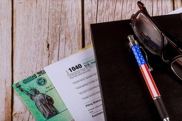 Mesa de trabajo en la oficina del contador formulario de impuesto sobre la renta individual 1040 con gafas y bolígrafo y cheque de reembolso