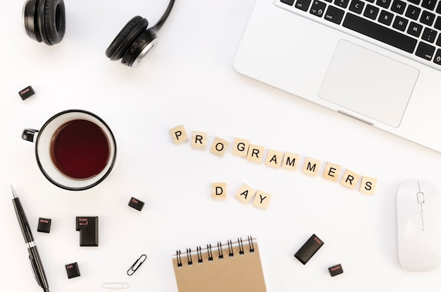 Mesa de trabajo de oficina con vista superior con laptop plateada y taza de café para el día internacional de los programadores