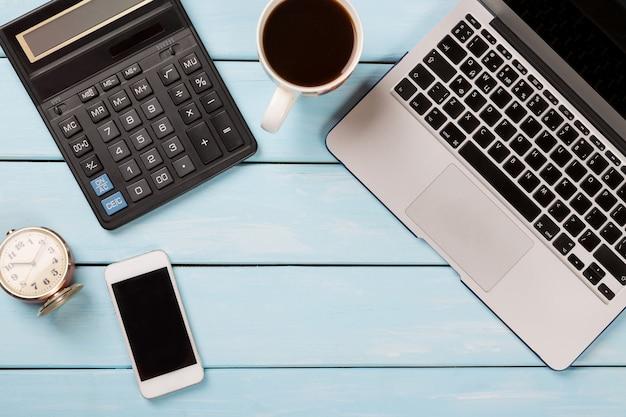 Mesa de trabajo con ordenador portátil, calculadora, teléfono moderno, café y despertador vintage en mesa de madera azul.