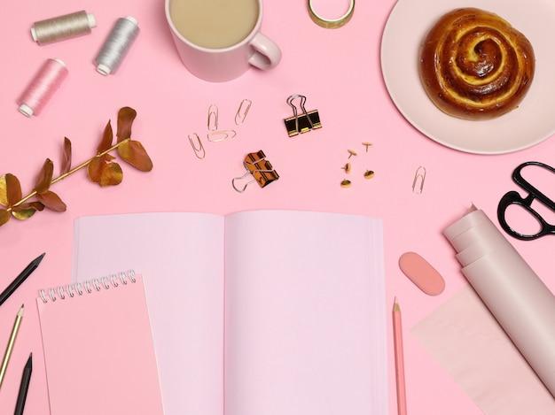 Mesa de trabajo rosa con papel de notas, accesorios de oficina, café, repostería.