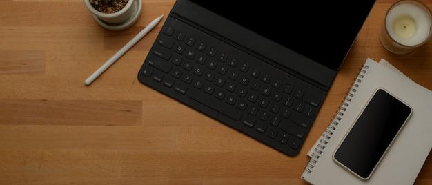 Mesa de trabajo rústica con tableta digital, teléfono inteligente, cuadernos, decoraciones