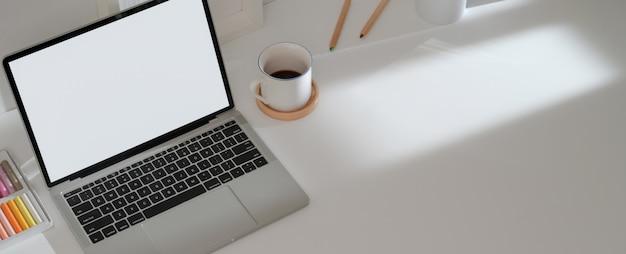 Mesa de trabajo simple con computadora portátil, taza de café, pasteles al óleo y espacio de copia en el escritorio blanco