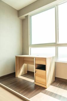 Mesa de trabajo vacía en la habitación con ventana