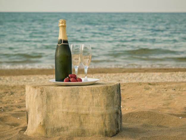 Mesa de un trozo de madera con una botella de champán y fresas junto al mar.