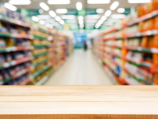 Mesa vacía de madera frente a supermercado borroso
