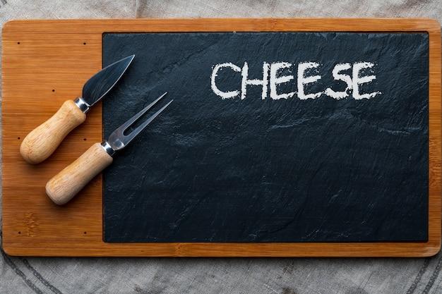 Mesa vacía para quesos y otras aberturas. copyspace (copia espacio) pizarra tenedor y cuchillo para queso. vista superior.